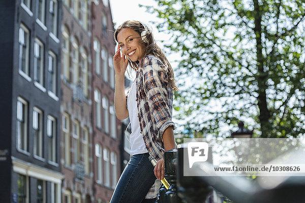 Niederlande  Amsterdam  lächelnde junge Frau mit Kopfhörer und Bierflasche auf Brücke