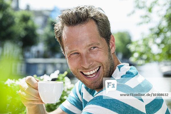 Niederlande  Amsterdam  glücklicher Mann trinkt eine Tasse Kaffee in einem Outdoor-Café