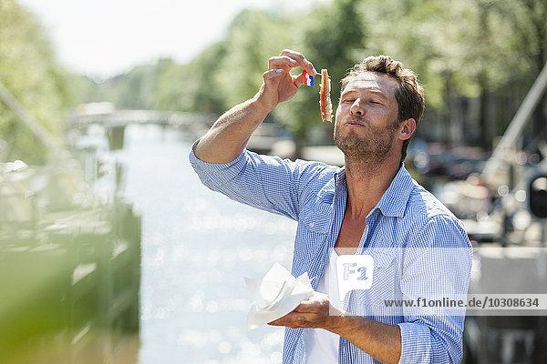 Niederlande  Amsterdam  Mann isst Matjeshering
