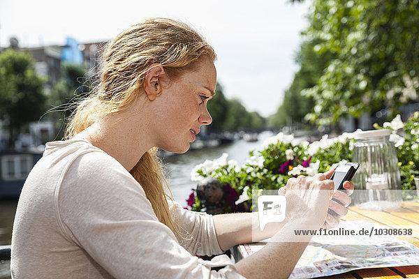 Niederlande  Amsterdam  Frau mit Handy im Outdoor-Café