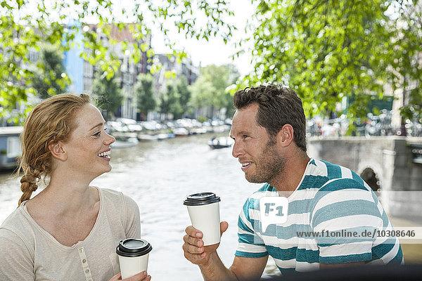 Niederlande  Amsterdam  Paar mit Kaffee am Stadtkanal