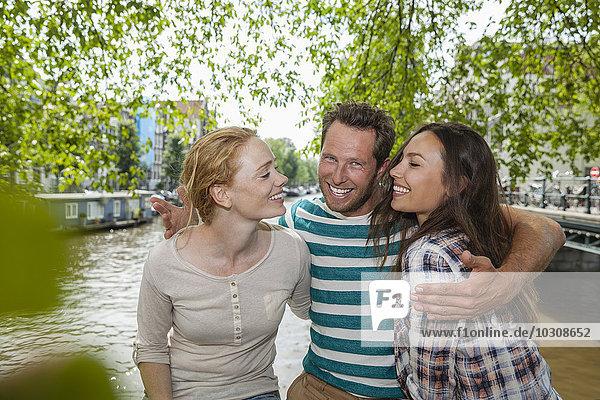 Niederlande  Amsterdam  glückliche Freunde am Stadtkanal