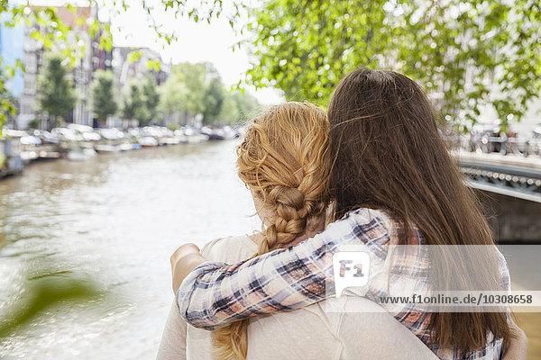 Niederlande  Amsterdam  zwei Frauen umarmen sich am Stadtkanal