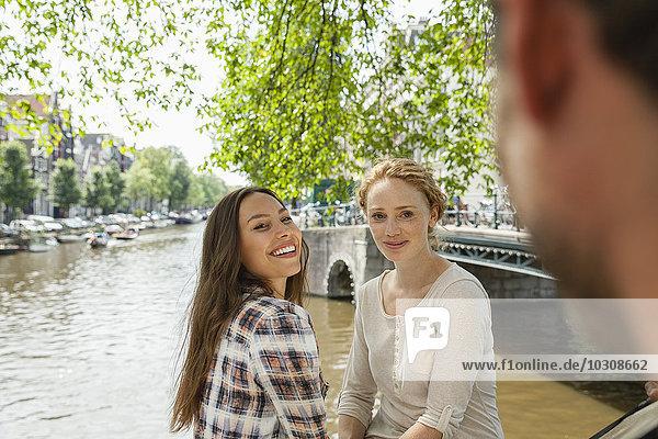 Niederlande  Amsterdam  zwei lächelnde Frauen am Stadtkanal