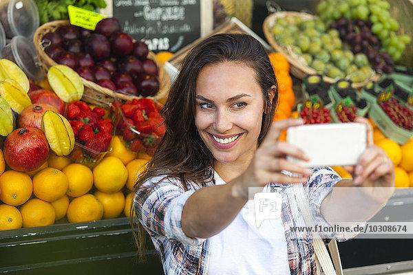 Lächelnde junge Frau  die einen Selfie im Gemüseladen nimmt