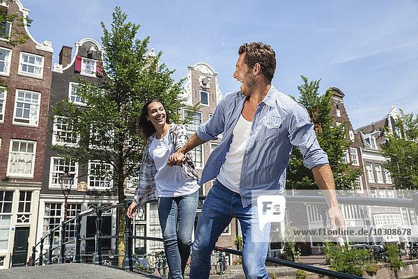 Niederlande  Amsterdam  glückliches Paar  das Hand in Hand auf einer Brücke läuft.