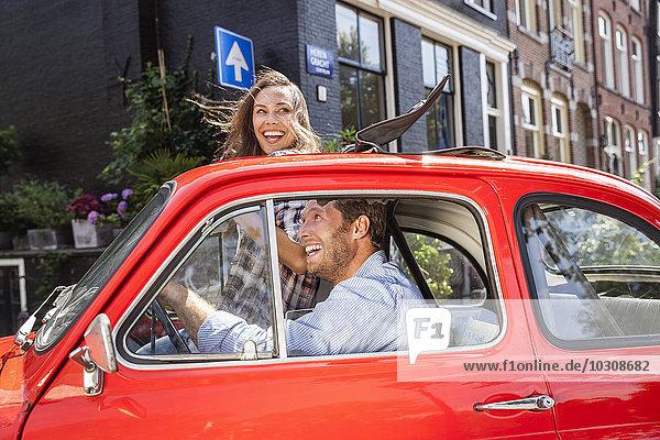 Niederlande  Amsterdam  glückliches Paar mit kleinem Auto in der Stadt