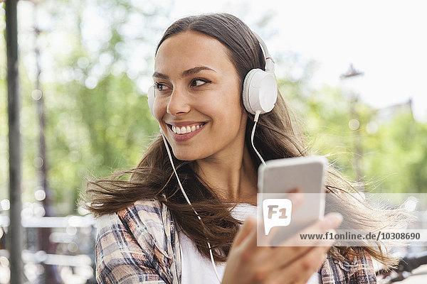 Glückliche junge Frau mit Kopfhörer und Handy im Freien