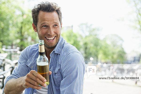 Niederlande  Amsterdam  glücklicher Mann trinkt Bier aus der Flasche