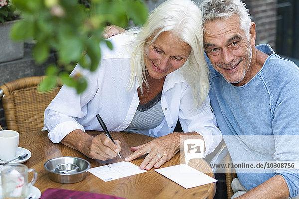 Seniorenpaar beim Schreiben von Postkarten im Outdoor-Café