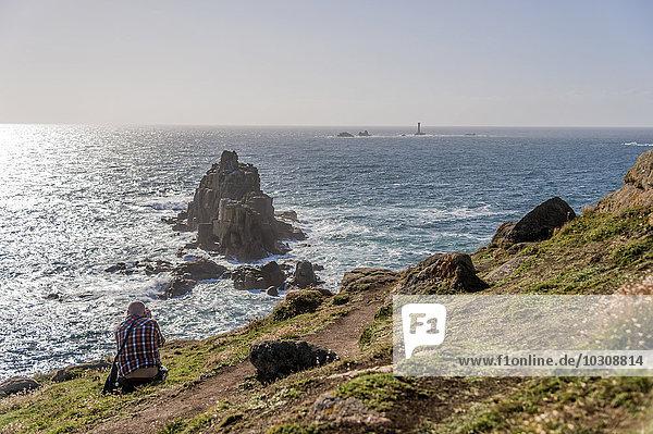 Großbritannien  England  Cornwall  Land's End  Fotograf beim Fotografieren von Armed Knight und Wols Rock Lighthouse