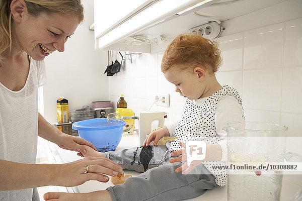 Kleines Mädchen sitzt auf dem Küchentisch und schaut auf gebrochenes Ei.