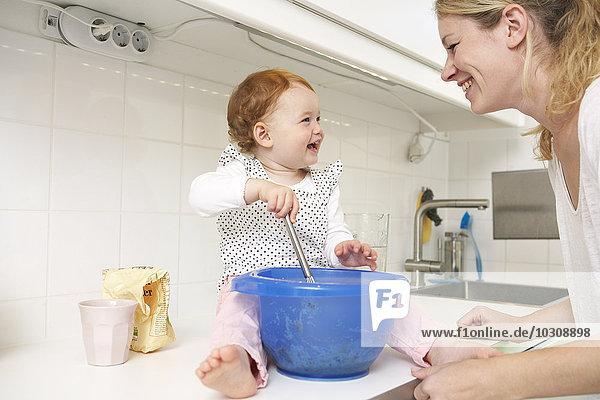 Mutter und kleine Tochter backen gemeinsam Kuchen in der Küche