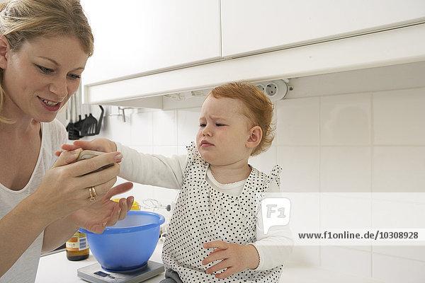 Mutter und kleine Tochter mit Smartphone in der Küche