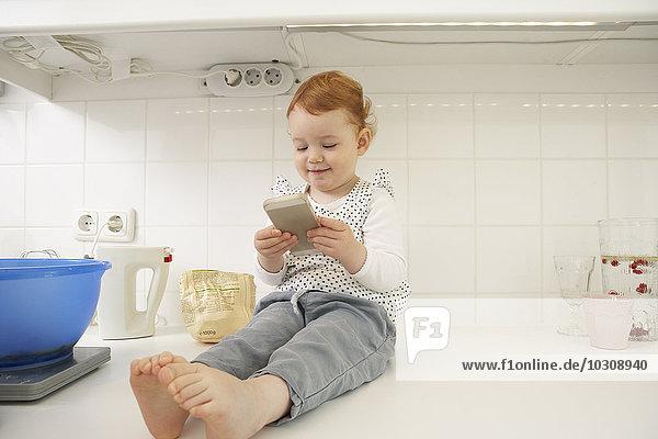Kleines Mädchen sitzend auf der Küchenzeile mit Smartphone