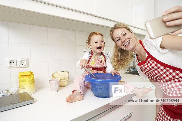 Junge Frau  die einen Selfie mit ihrer kleinen Tochter in die Küche nimmt
