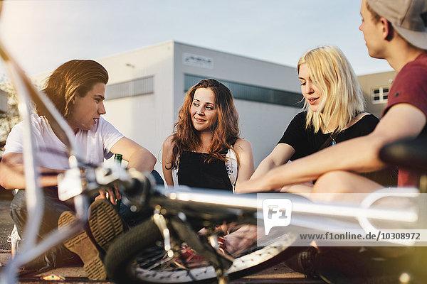 Fröhliche Freunde sitzen zusammen im Freien