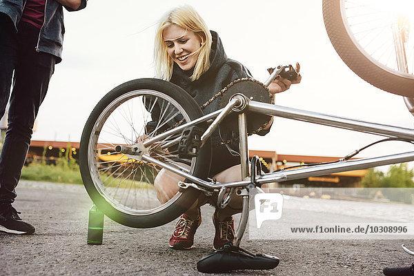 Junge Frau repariert BMX-Fahrrad