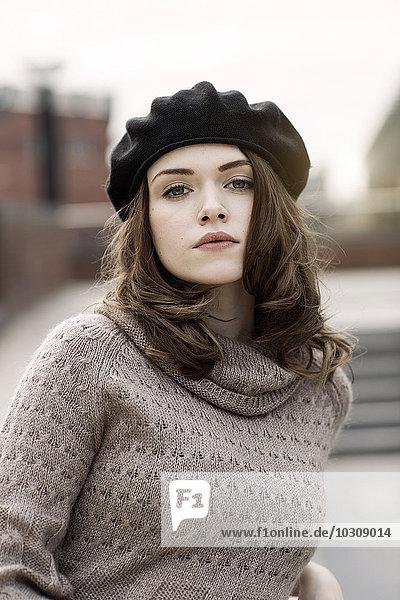 Porträt einer jungen Frau mit Baskenmütze und Strickkleid