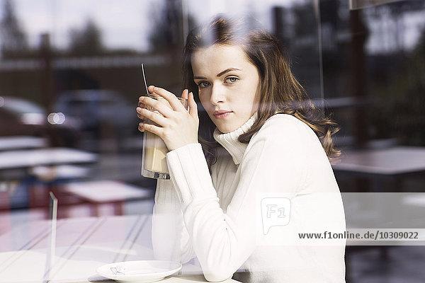 Porträt einer jungen Frau mit Latte Macchiato in einem Café mit Blick durch die Fensterscheibe