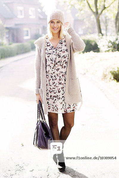 Porträt einer lächelnden blonden Frau in gemustertem Kleid  Strickjacke und Wollmütze