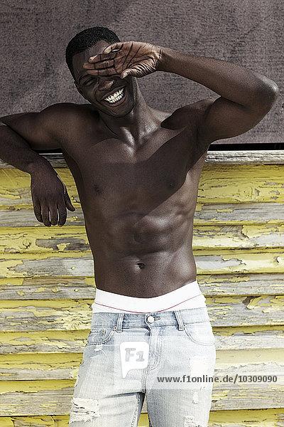 Porträt eines lachenden jungen Mannes vor der Holzwand