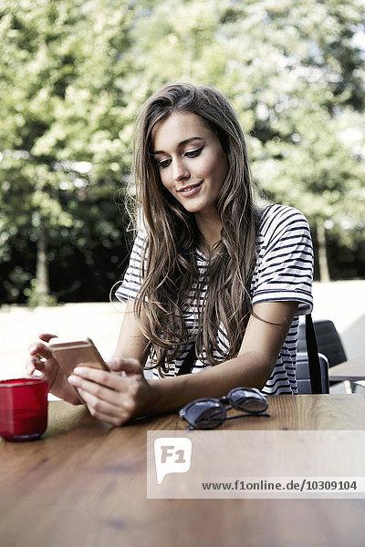 Porträt einer jungen Frau am Tisch mit Blick auf das Smartphone