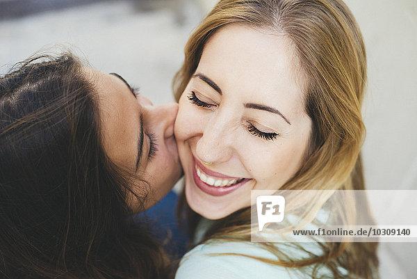 Mädchen küsst junge Frau auf die Wange