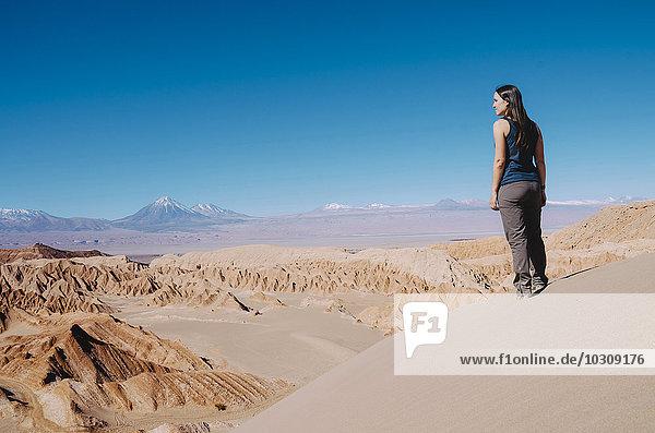 Chile  Atacama-Wüste  Frau auf einer Düne stehend mit Blick auf die Aussicht