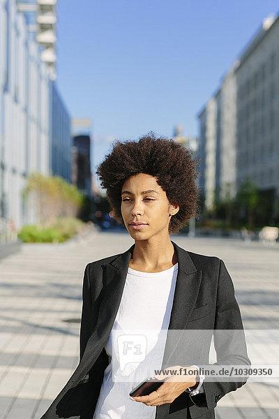 USA  New York City  Portrait einer Geschäftsfrau mit Smartphone