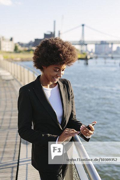 USA  New York City  lächelnde Geschäftsfrau mit Blick auf ihr Smartphone