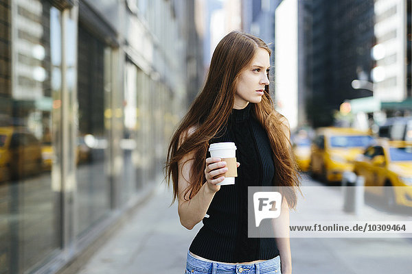 USA  New York City  portrait of young woman with coffee to go