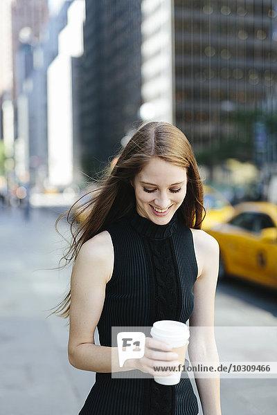 USA  New York City  Portrait einer lächelnden jungen Frau mit Kaffee zum Mitnehmen
