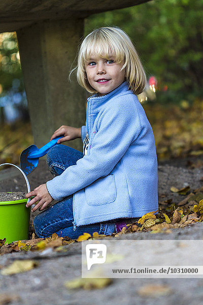 Portrait of little girl playing with sandbox toys