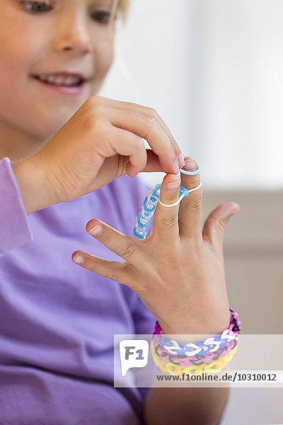 Little girl making loom bracelets