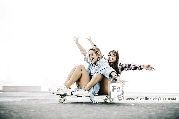 Zwei junge Frauen auf einem Longboard unterwegs