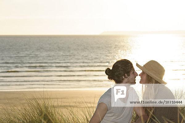 Junges Paar sitzt an Stranddünen vor dem Atlantik