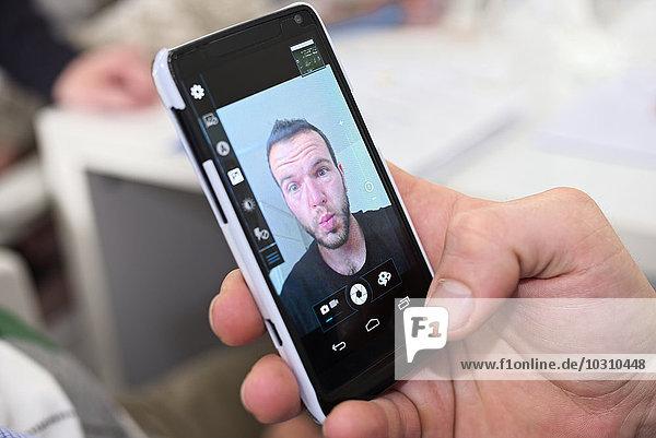 Selfie des jungen Mannes auf dem Handy-Display