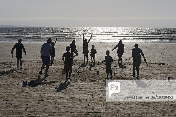 Zwei Gruppen spielen Kubb am Strand in der Abenddämmerung.