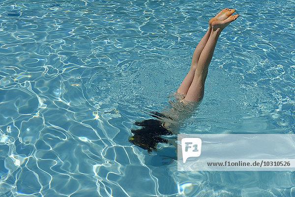 Mädchen beim Handstand im Schwimmbad