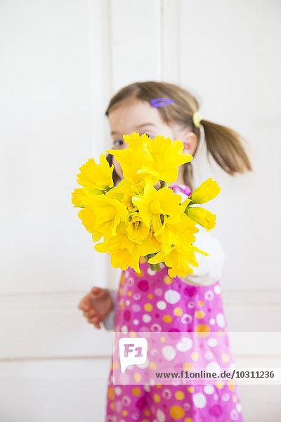 Kleines Mädchen mit Narzissenbüschel