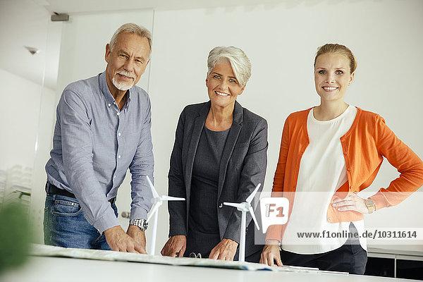 Drei lächelnde Geschäftsleute mit Windkraftanlagenmodell auf dem Konferenztisch