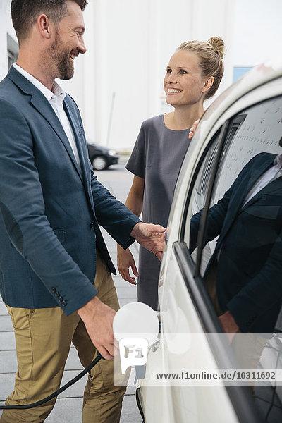 Mann und Frau beim Aufladen des Elektroautos im Gespräch