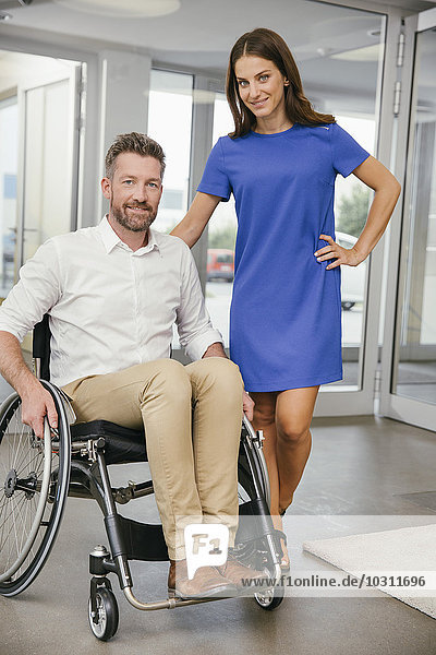 Mann im Rollstuhl mit seiner Freundin  glücklich lächelnd