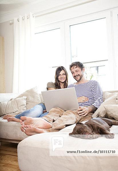 Lächelndes Paar entspannt mit Laptop auf der Couch im Wohnzimmer