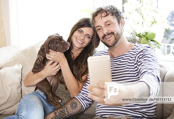 Paar sitzend mit Olde English Bulldogge auf der Couch mit einem Selfie mit Smartphone