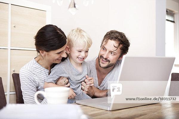 Eltern und ihr kleiner Sohn sitzen am Holztisch mit Laptop