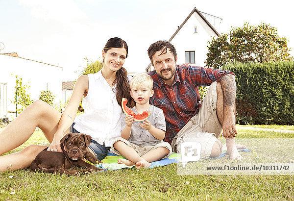 Eltern sitzen mit ihrem kleinen Sohn und Hund auf einer Decke im Garten.