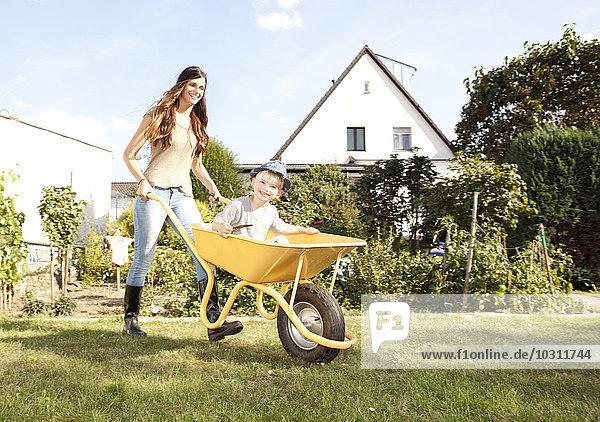 Frau mit ihrem kleinen Sohn in einer Schubkarre sitzend