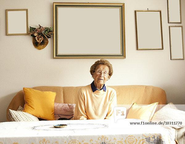 Porträt einer alten Frau  die auf der Couch in ihrem Wohnzimmer sitzt.